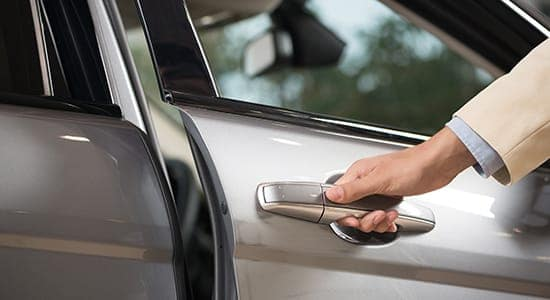 picture of person's hand opening car door handle