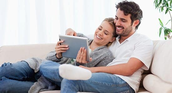 Happy couple on couch online shopping on a tablet