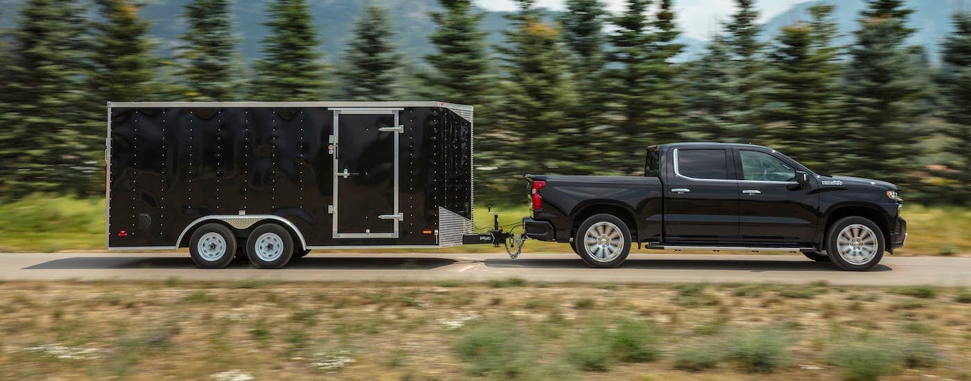A black 2020 Chevy Silverado 1500 High Country is shown from the side towing a black enclosed trailer.