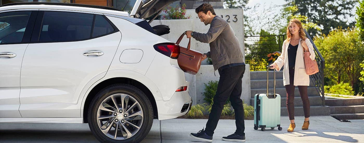 A man is loading cargo into the rear of a white 2020 Buick Encore GX.