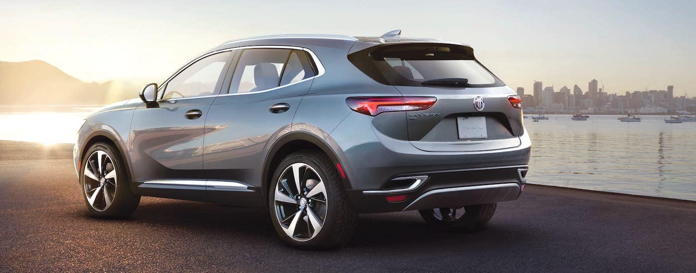 A gray 2021 Buick Envision is shown from the rear in front of a river and city.