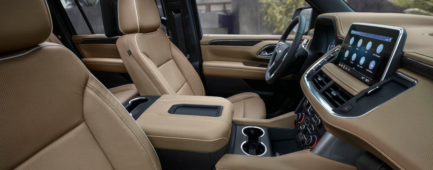 The tan interior of a 2021 Chevy Suburban is shown from the passenger-side window.