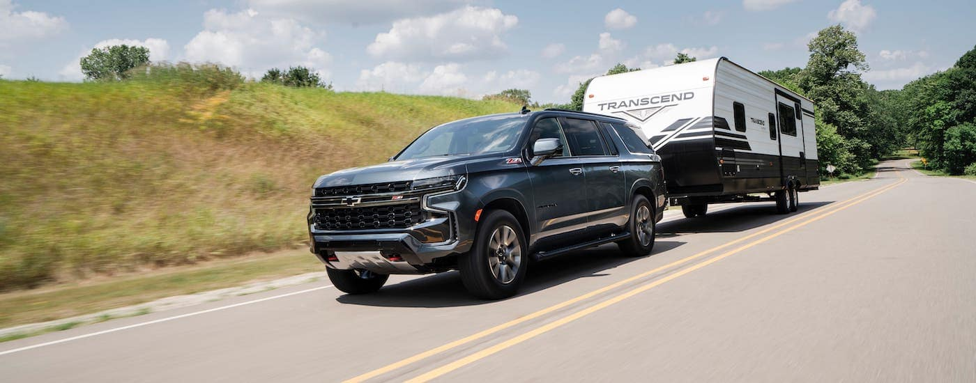 A gray 2021 Chevy Suburban Z71 is towing a camper on a highway near Lexington, KY.