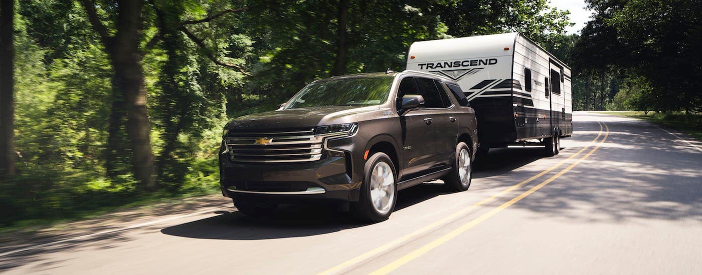 A gray 2021 Chevy Tahoe High Country is towing a camper on a rural highway near Lexington, KY.