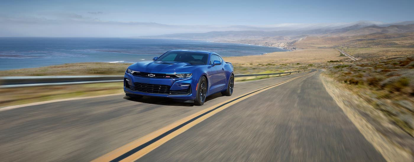 A blue 2020 Chevy Camaro SS from a Chevy dealer near you is driving on a coastal highway.