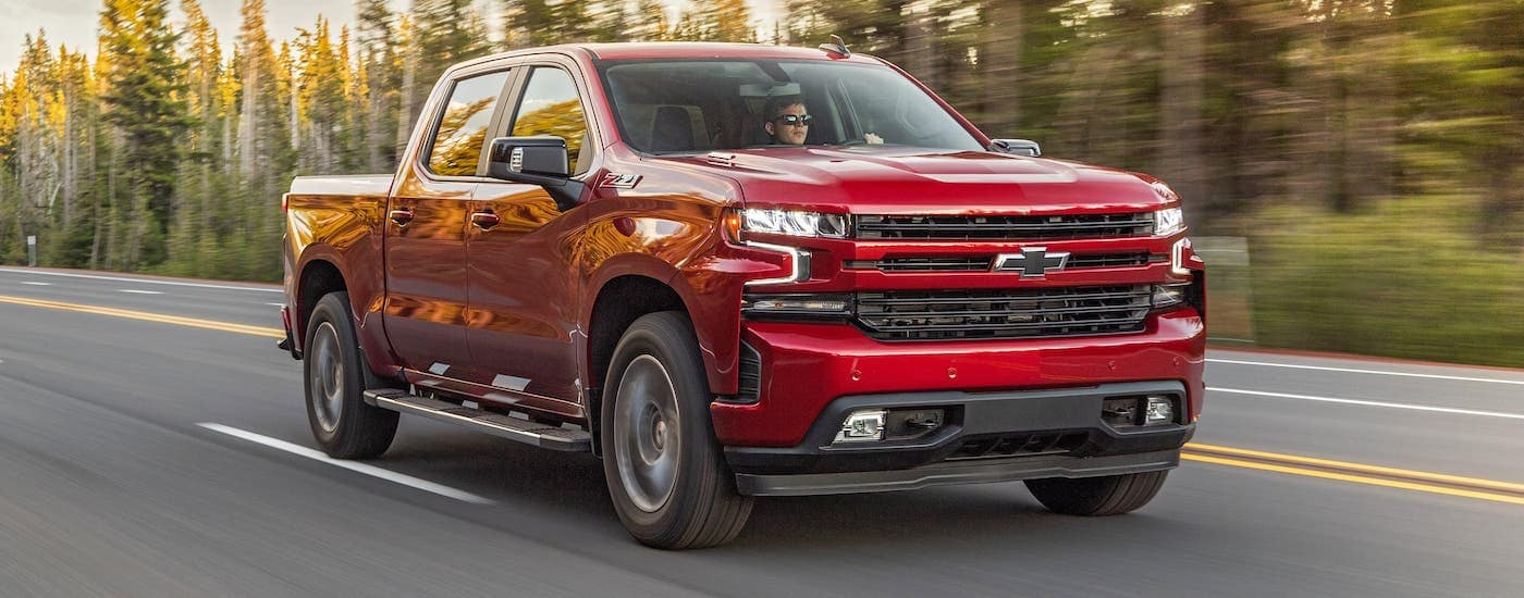 A red 2020 Chevy Silverado 1500 is driving on a highway near Lexington, KY.