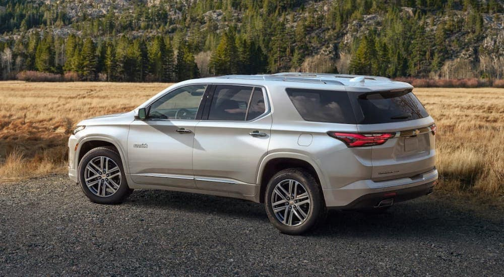 A silver 2022 Chevy Traverse High Country is parked in front of a field.