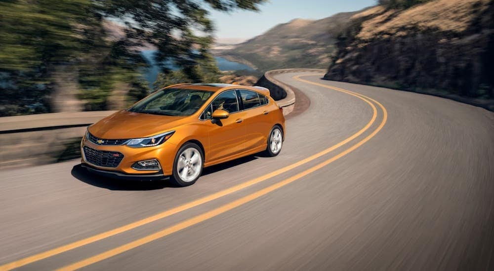 An orange 2018 Chevy Cruze Hatchback is driving around a corner past a lake and mountains.