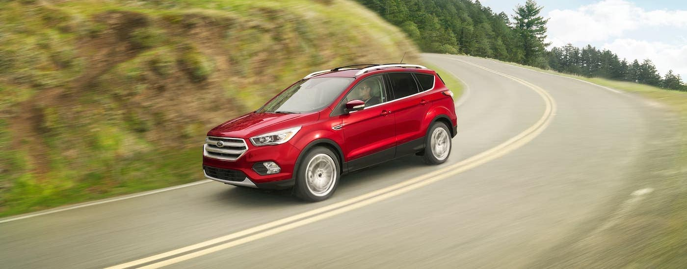 A red 2018 Ford Escape is driving on a mountain highway.