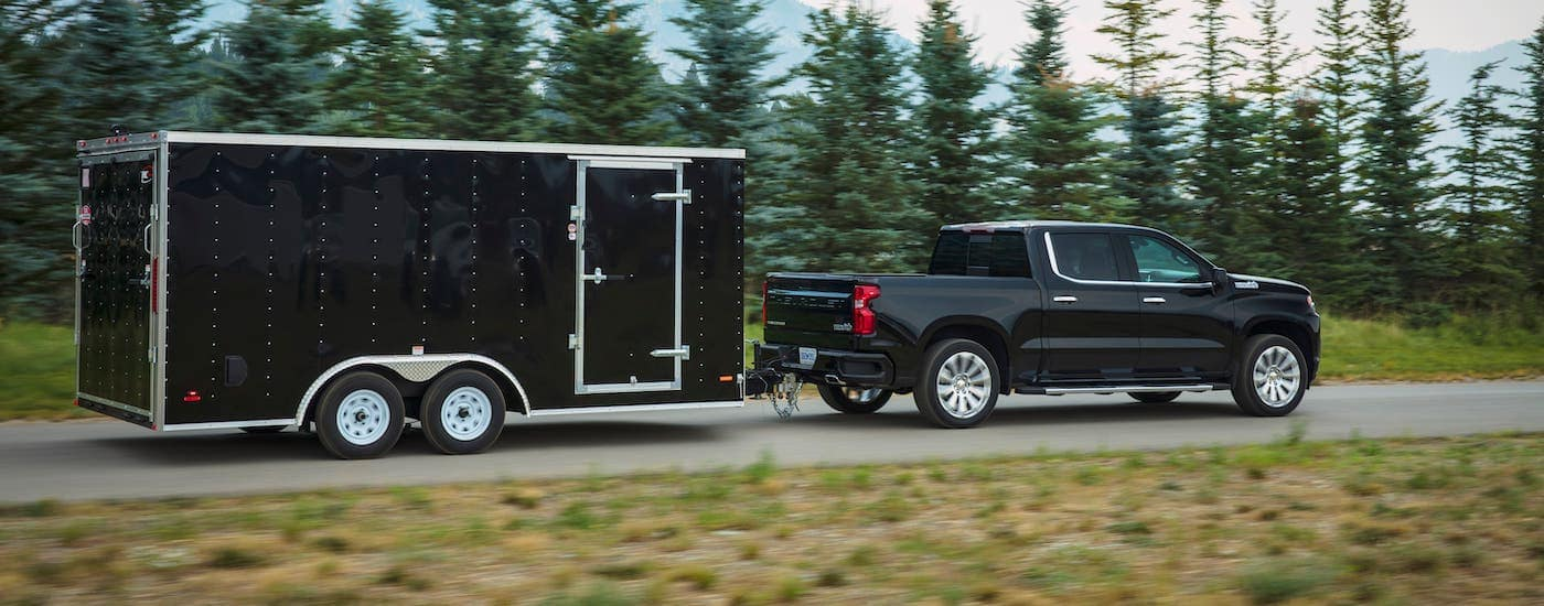A black 2019 Chevy Silverado High Country is towing a black enclosed trailer near Lexington, KY.