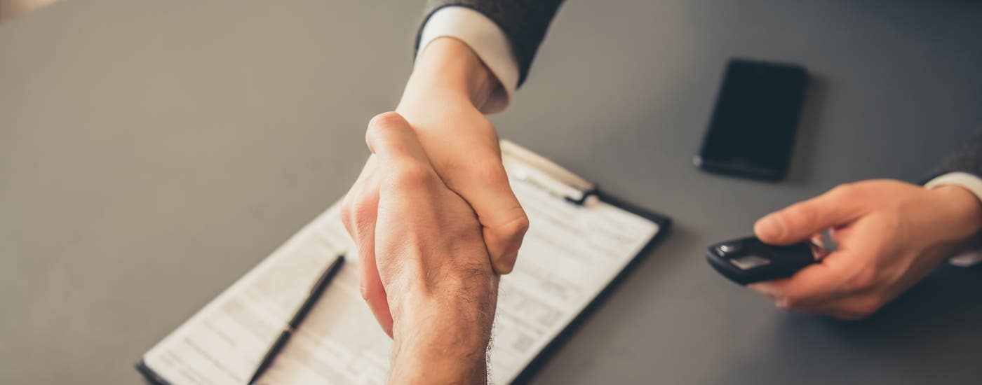 Hands are shaking over paperwork while handing over car keys at a used car dealer near you.
