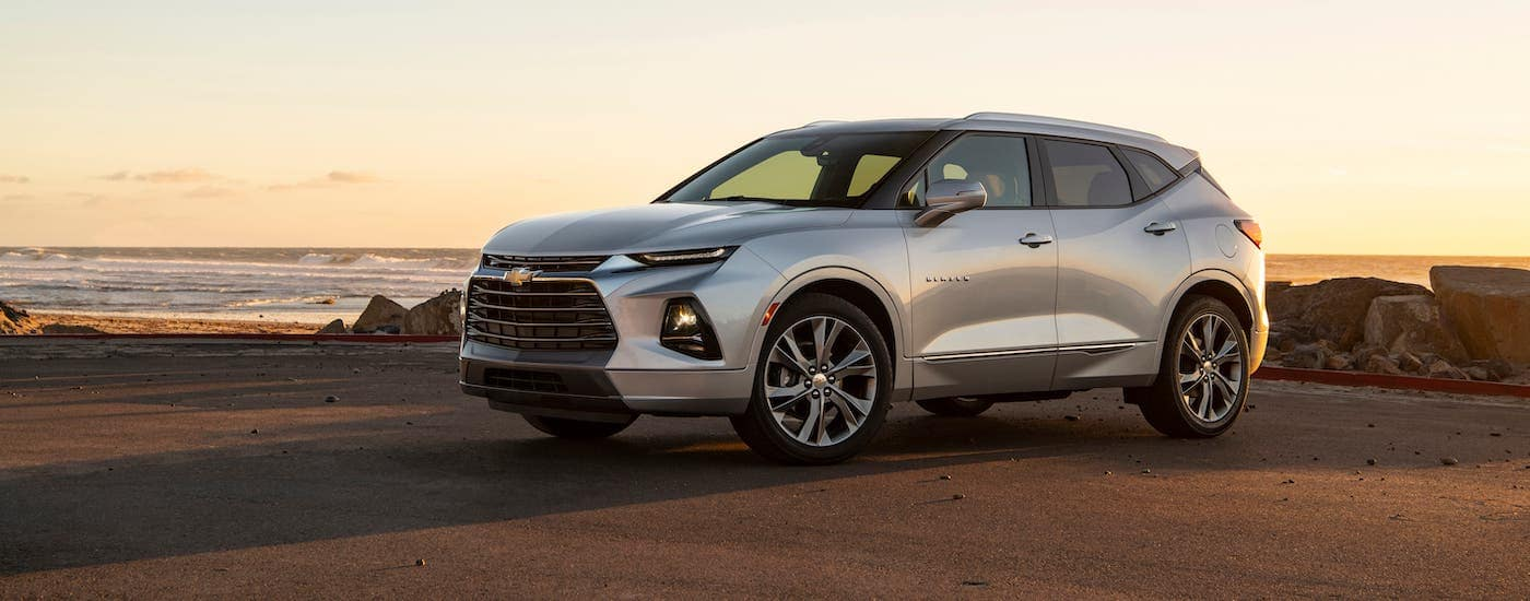 A silver 2020 Chevy Blazer Premier is parked at a beach at sunset.