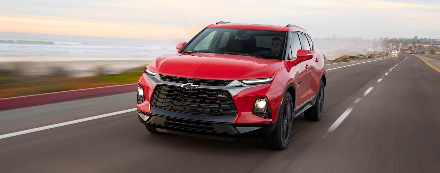 A red 2020 Chevy Blazer RS is driving on a coastal highway.
