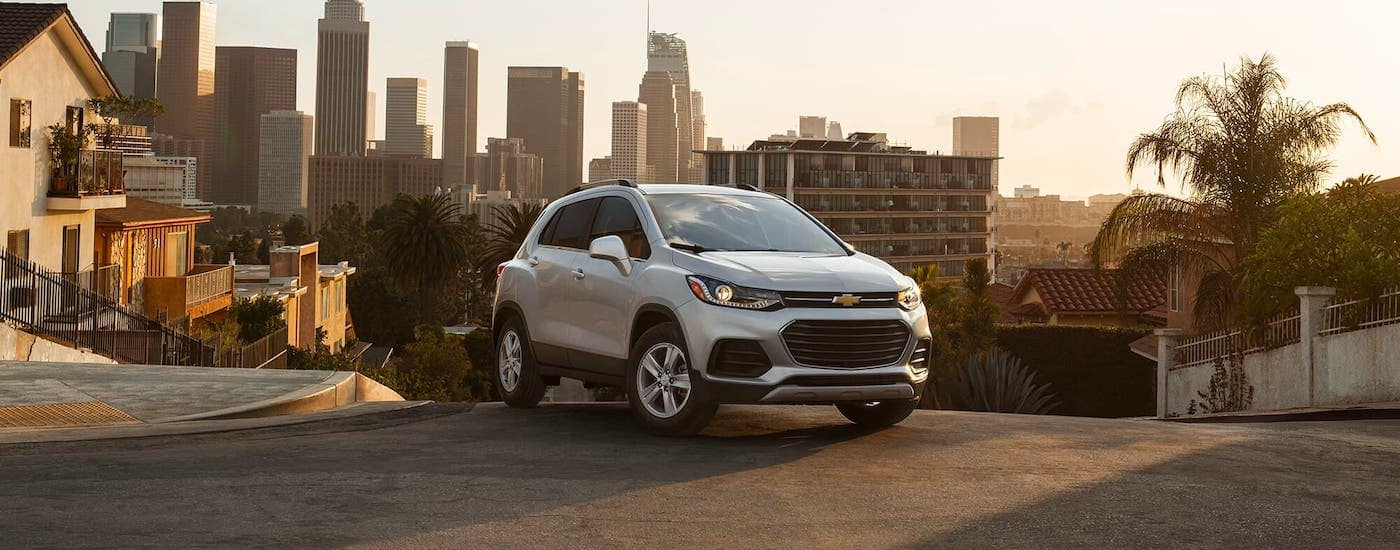 A silver 2021 Chevy Trax is parked on a hill in front of a city at sunset.