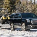 A black 2019 GMC Yukon Denali is towing snowmobiles on a snowy road.