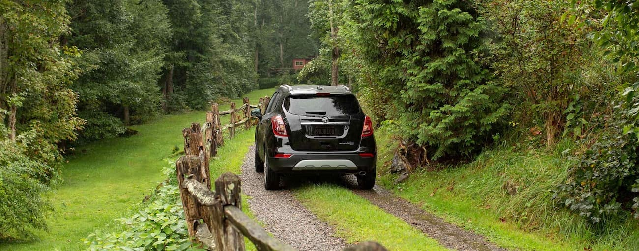 A black 2021 Buick Encore is driving away on a dirt path in the woods.