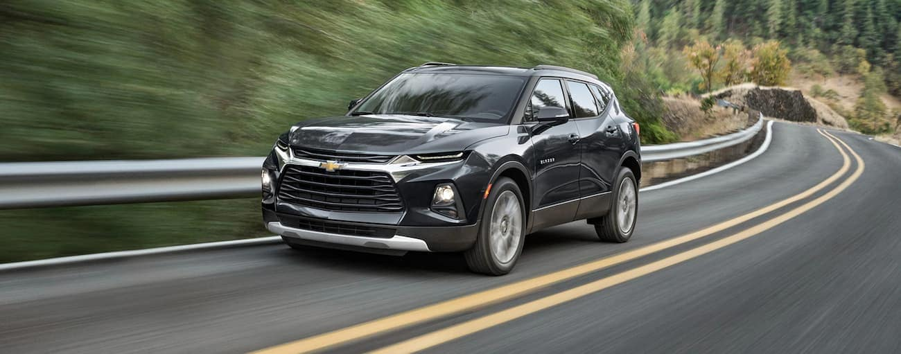 A black 2021 Chevy Blazer is driving past a guard rail and trees.