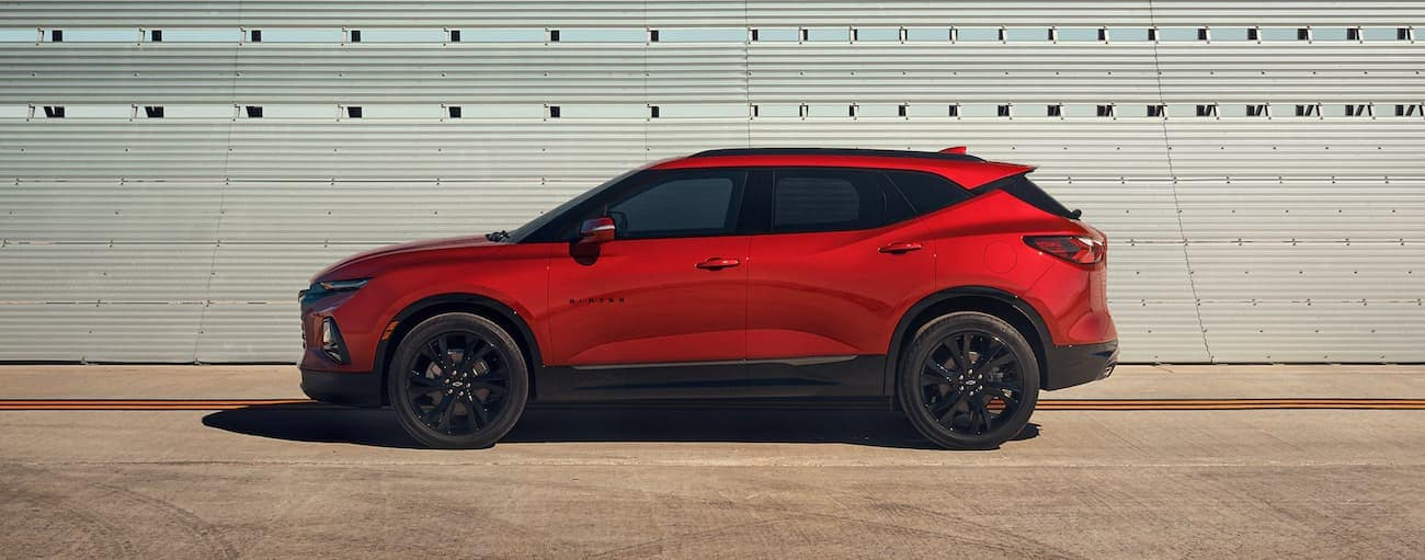 A red 2021 Chevy Blazer RS is parked in front of a white wall.
