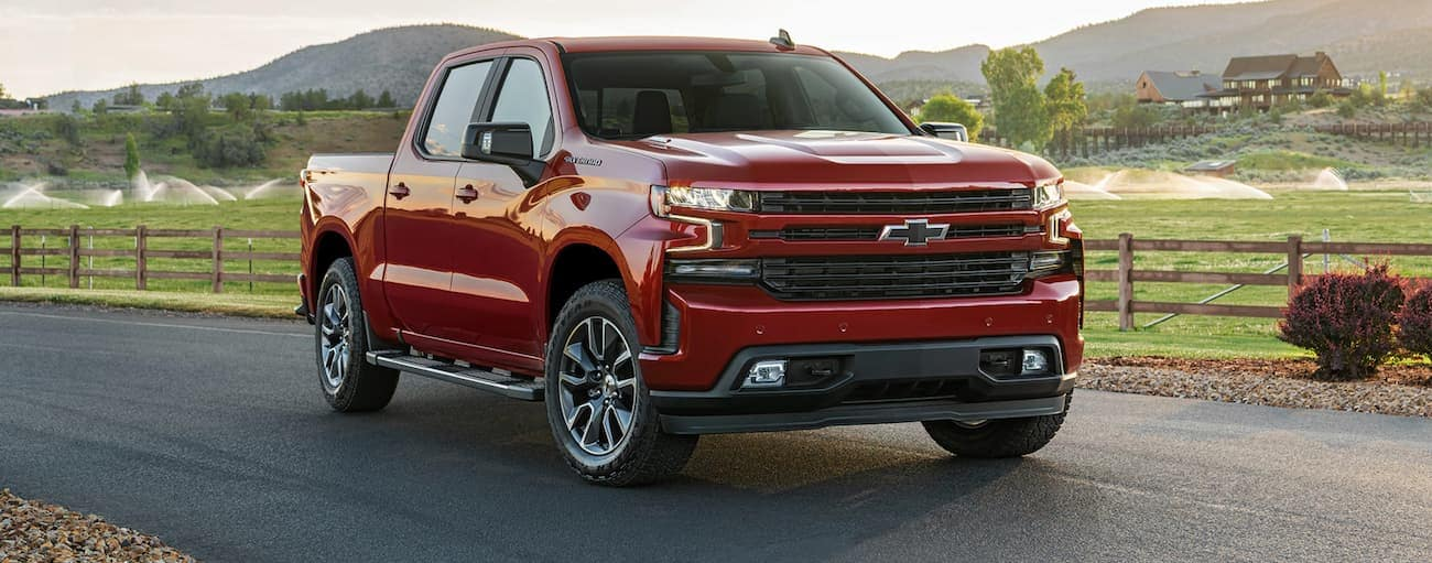 A red 2021 Chevy Silverado 1500 is parked in front of a farm and hills.