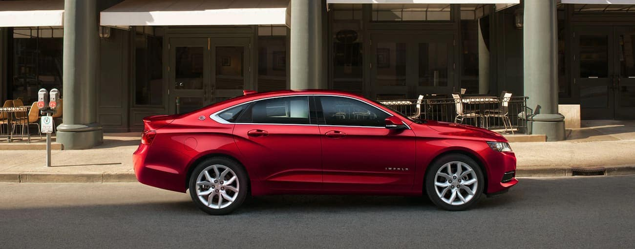 A red 2020 Chevy Impala is parked on a city street in front of a cafe.