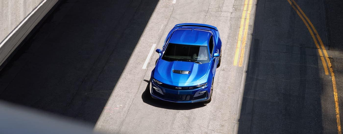 A blue 2021 Chevy Camaro is shown from above while driving on a highway.
