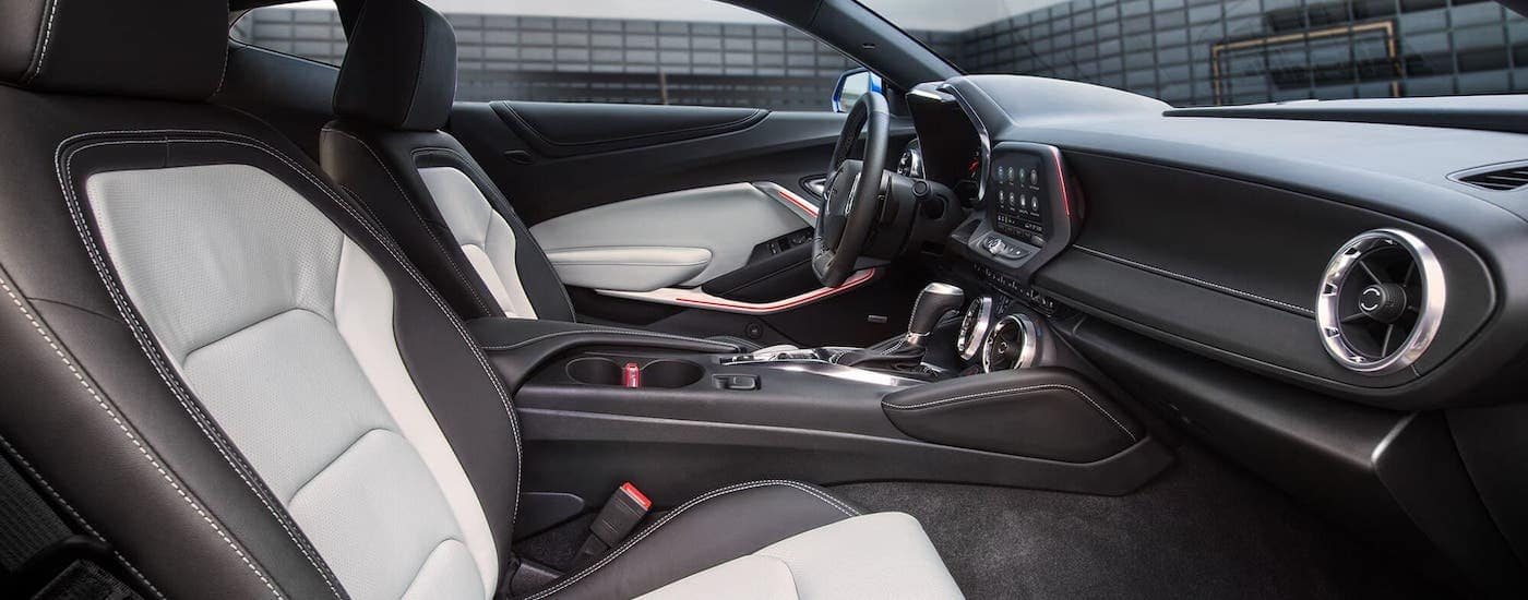 The white and black interior of a 2021 Chevy Camaro is shown from the passenger seat.