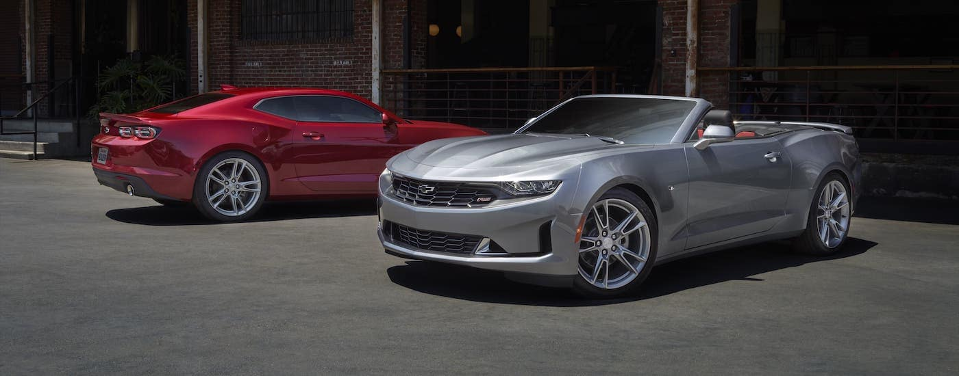 A red 2021 Chevy Camaro LS and a silver LT convertible are parked in front of a brick building.
