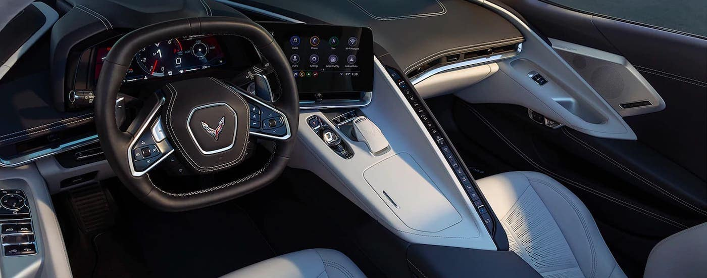 A white and black interior of a 2021 Chevy Corvette is shown from the driver's perspective.