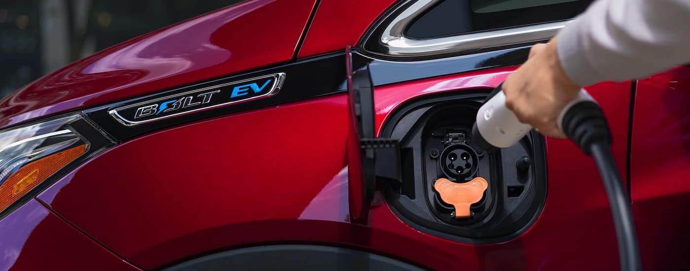 A close up is shown of the charging port on a red 2021 Chevy Bolt EV.