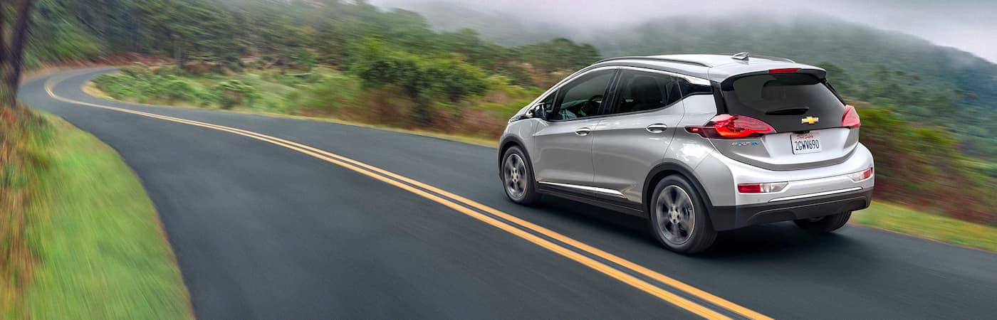 A silver 2021 Chevy Bolt EV is shown from the side driving down a foggy road.