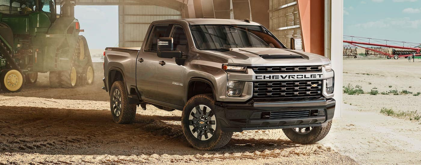 A tan 2021 Chevy Silverado 2500HD is parked in a metal barn next to farming equipment.