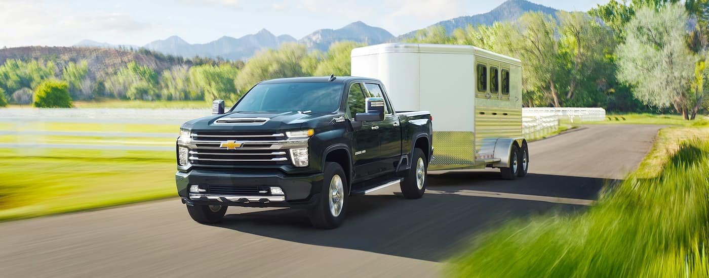 A black 2021 Chevy Silverado 2500HD is towing a trailer past a fence and field.
