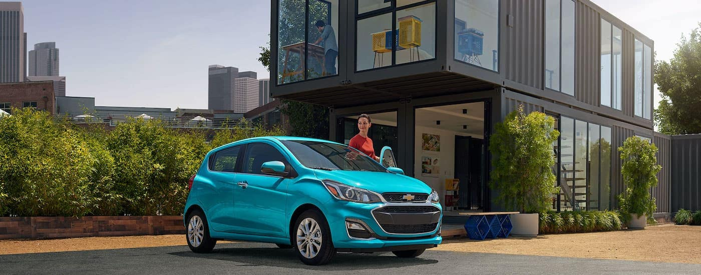A teal 2021 Chevy Spark is parked in front of a shipping container home.