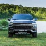 A gray 2021 Chevy Suburban is shown from the front parked in front of a lake.