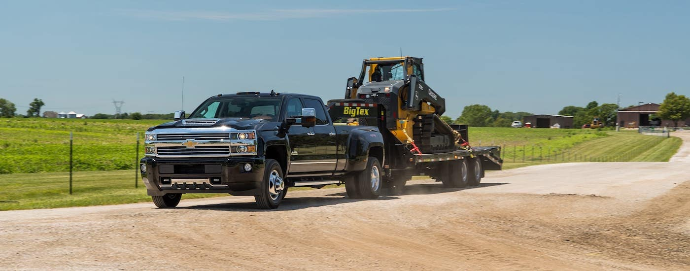 A black 2018 Chevy Silverado 3500 is towing construction equipment on a dirt road.