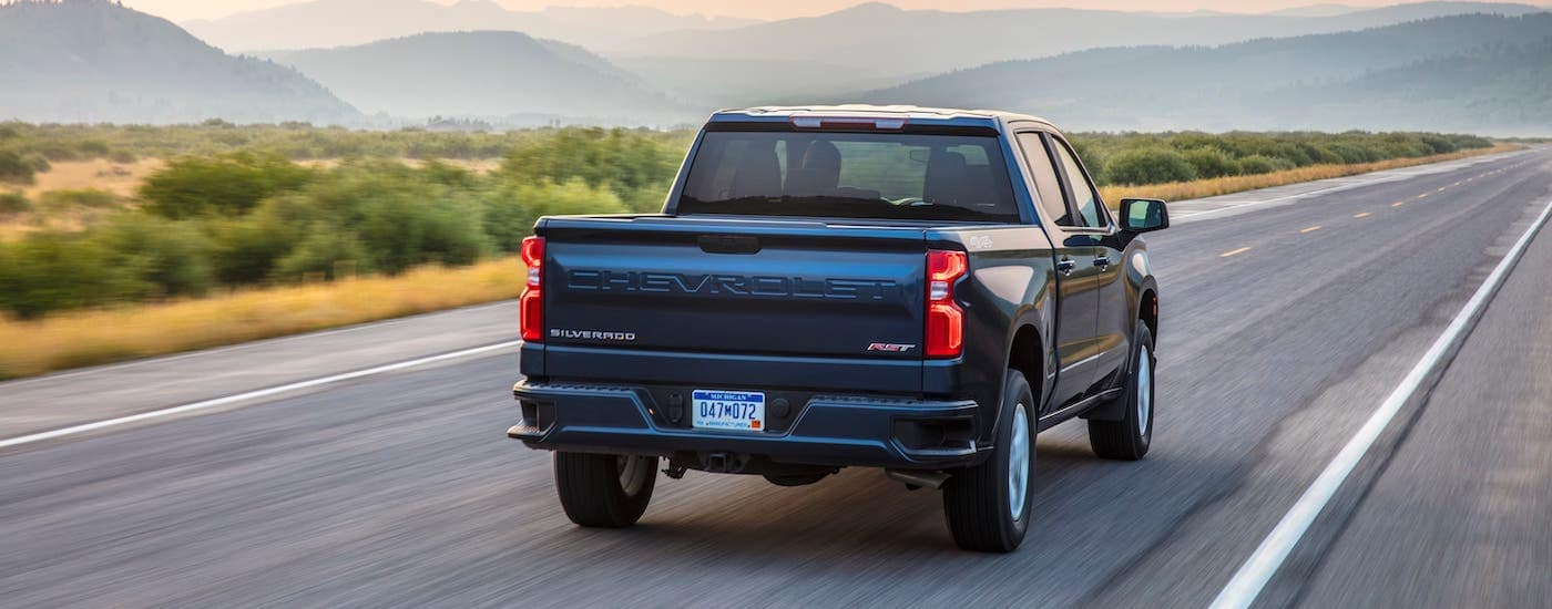 A blue 2019 Chevy Silverado 1500 RST is shown from the rear driving on a highway towards misty mountains.