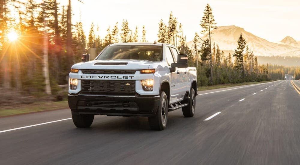 A white 2020 Chevy Silverado 2500HD Custom from a used truck dealer is driving on a highway past evergreen trees.