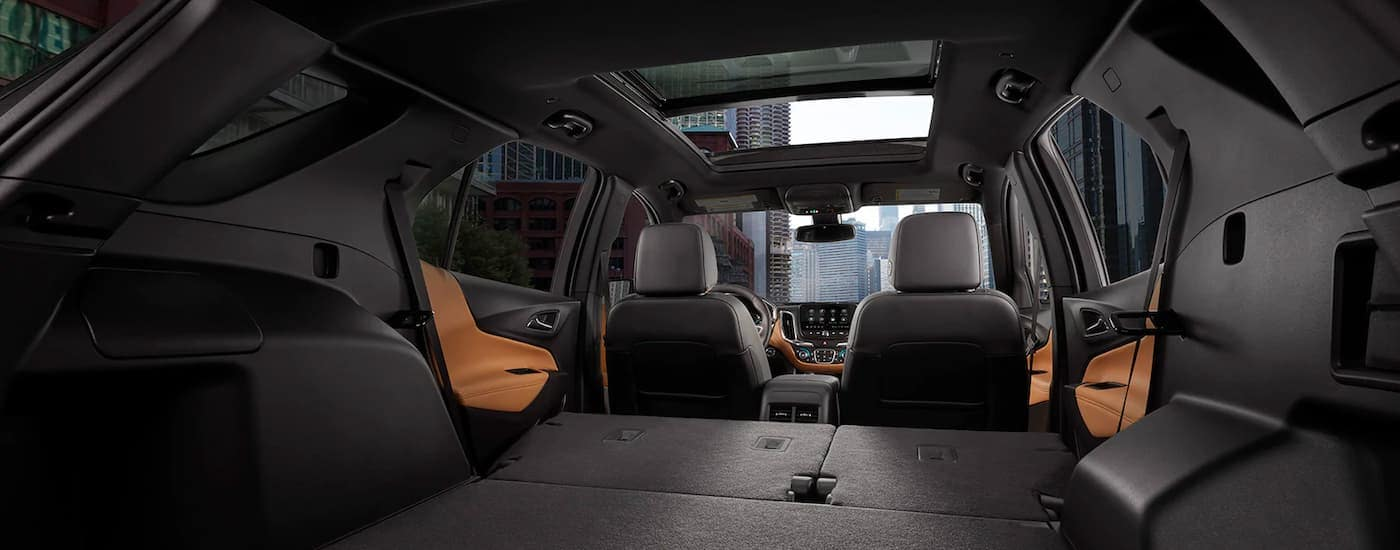 The black and brown interior is shown from behind at a low angle on a 2021 Chevy Equinox.