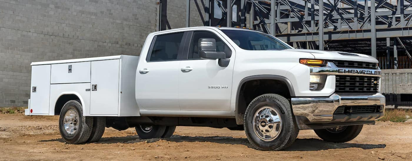 A white 2021 Chevy Silverado 3500 HD Chassis Cab is shown from the side parked in front of a cinder block wall.
