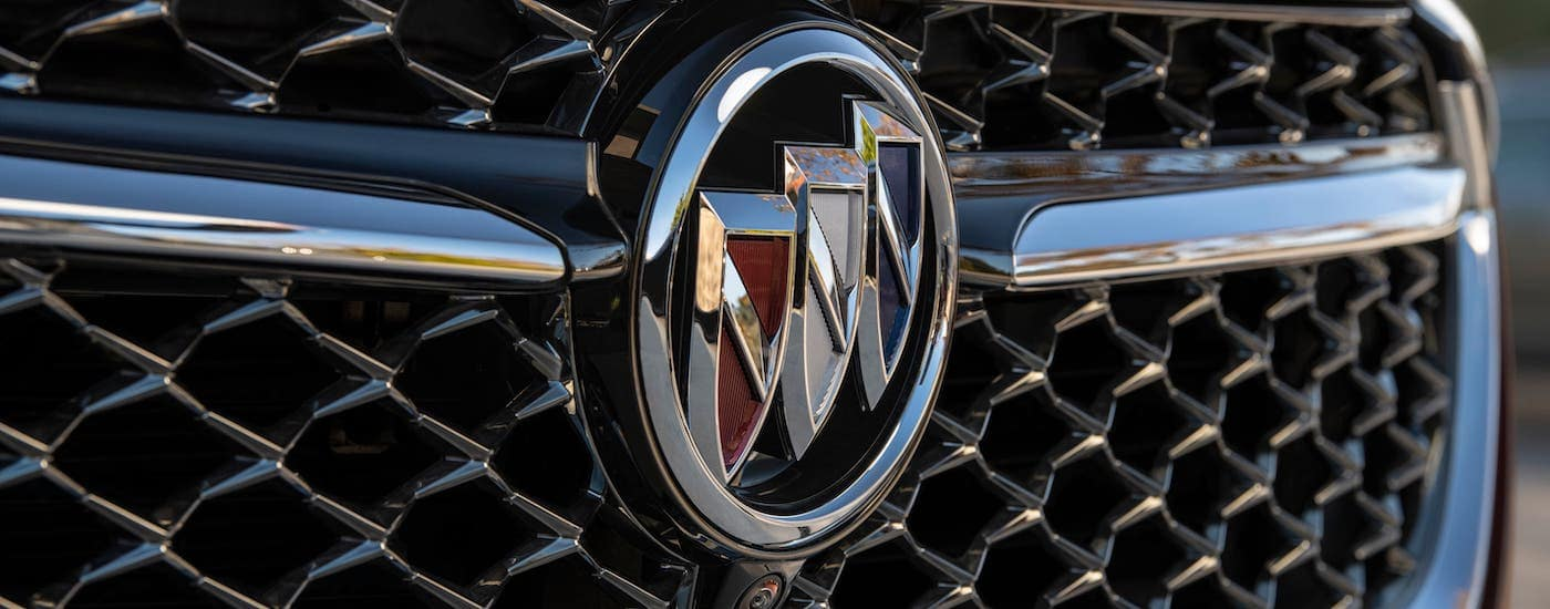 A closeup shows the Buick logo on the grille of a burgundy 2021 Buick Envision Avenir.