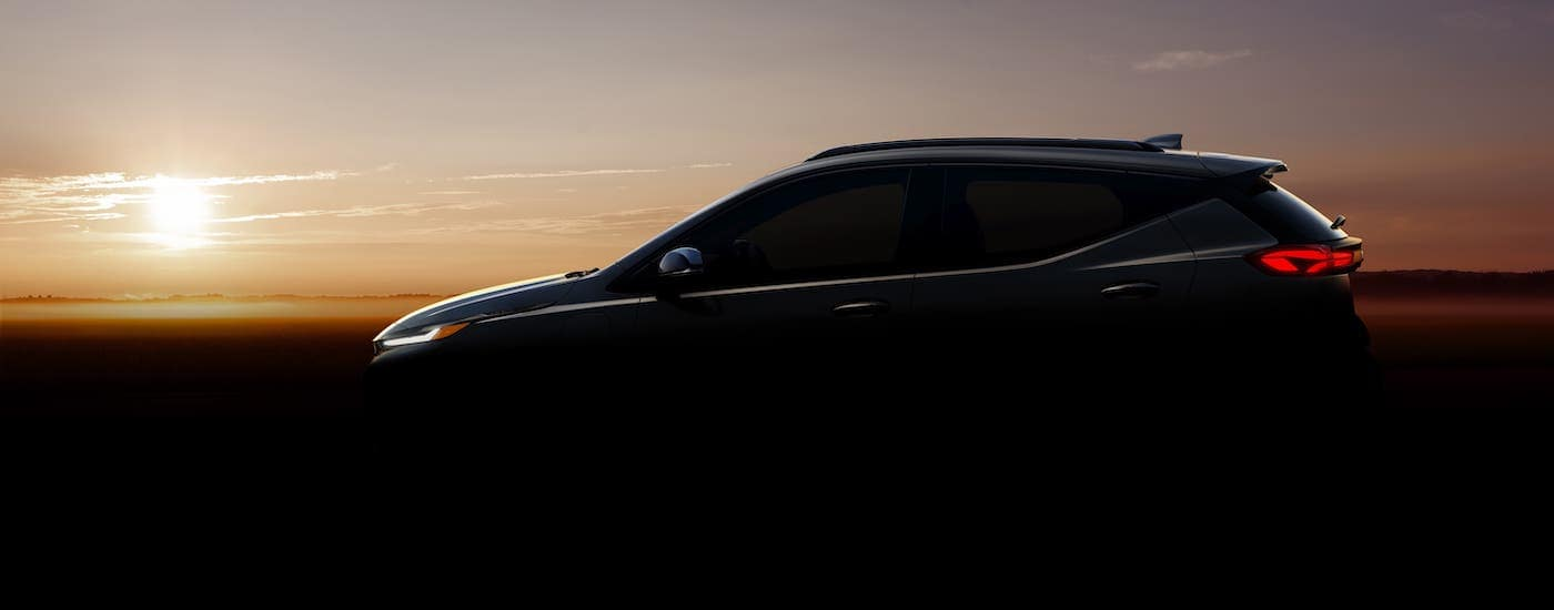 A silhouette of a Chevy Bolt EUV shown at sunset.