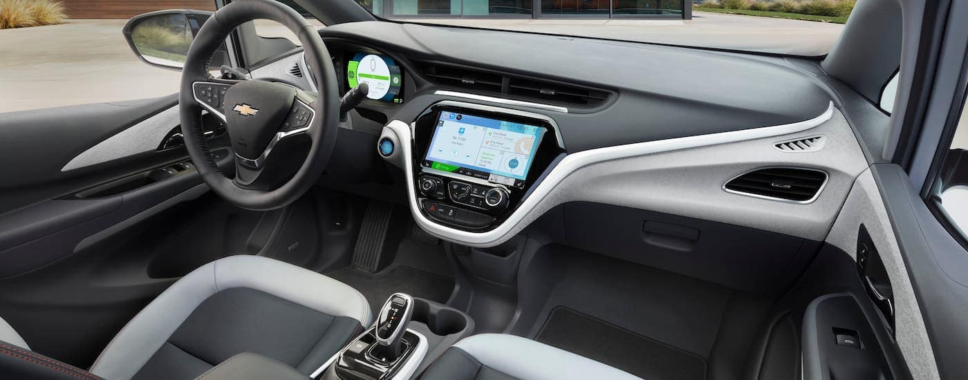 The gray and black interior and front seats of a 2021 Chevy Bolt EV are shown.