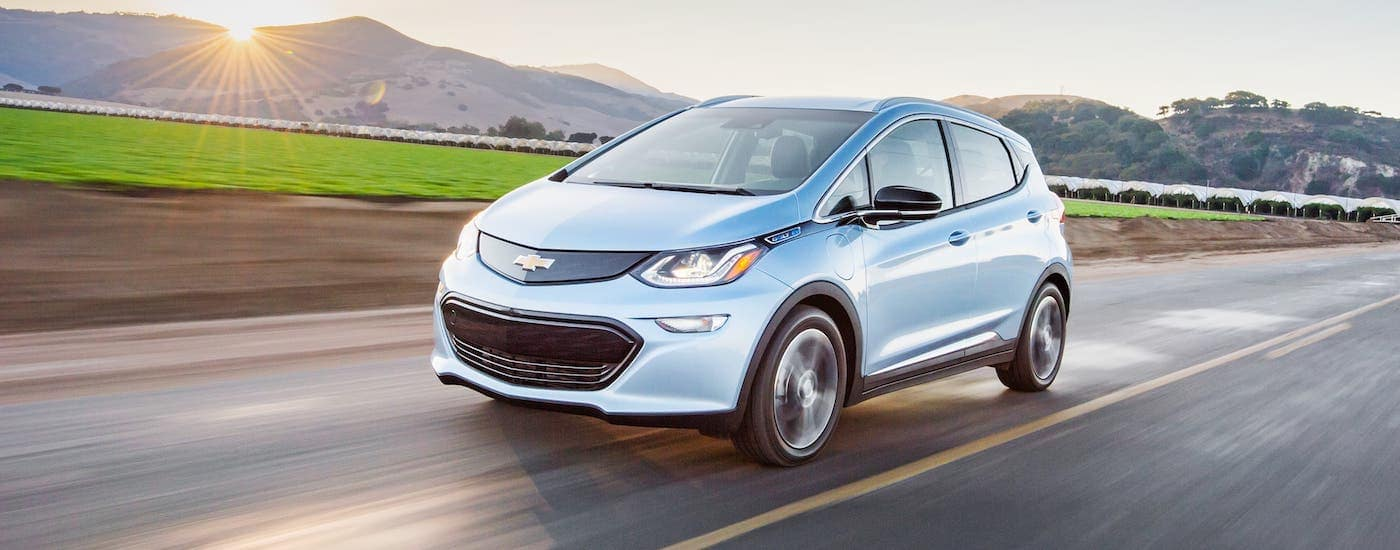 A silver electric vehicle, a 2021 Chevy Bolt EV, is driving on a highway.