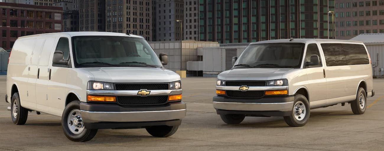 A white and a silver 2021 Chevy Express Van are parked in front of city buildings.