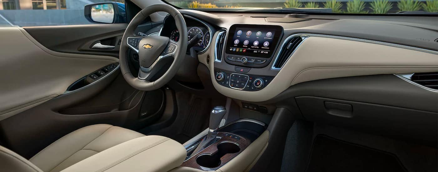 The black and beige interior and fronts seats are shown from the side in a 2021 Chevy Malibu.