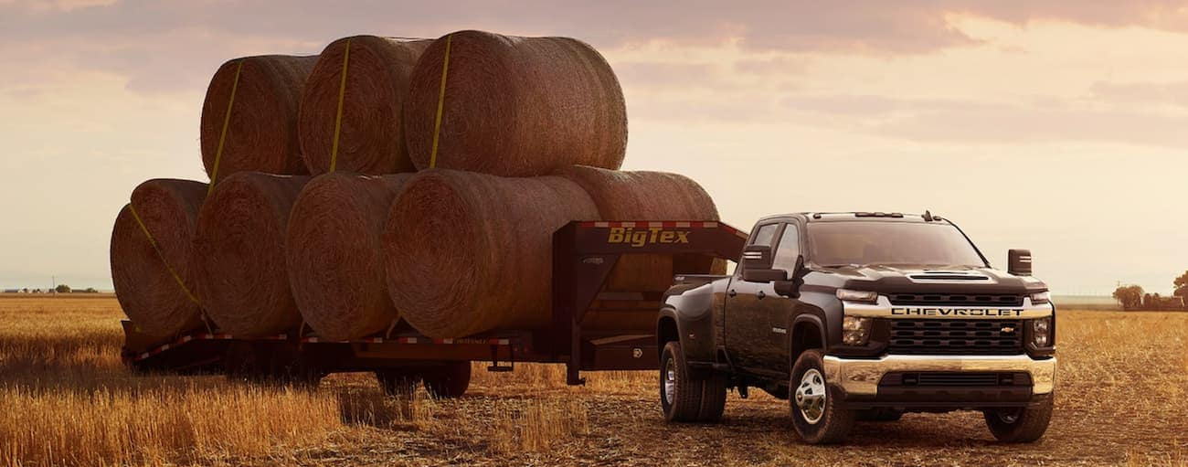 A black 2021 Chevy Silverado 3500HD is in a field at sunset with a trailer full of hay bales.