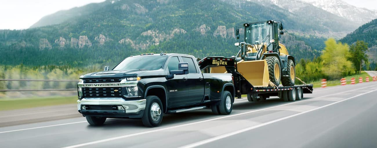 A black 2021 Chevy Silverado 3500HD is towing equipment past hills.