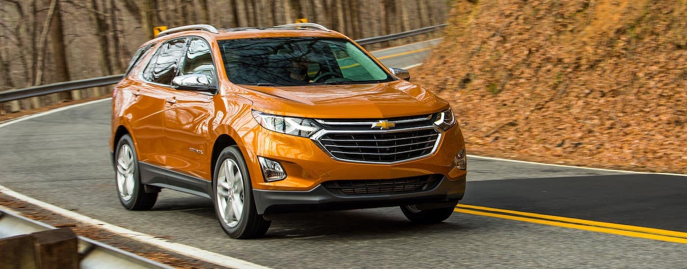 An orange 2021 Chevy Equinox is driving around a curving road in the fall.