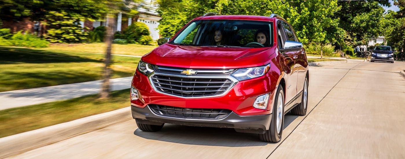 A red 2021 Chevy Equinox is driving on a suburban road after winning the 2021 Chevy Equinox vs 2021 Toyota RAV4 comparison.