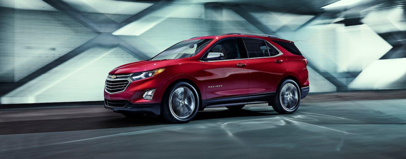 A dark red 2021 Chevy Equinox is driving in a tunnel at night.